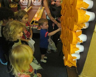 Neighbors | Alexis Bartolomucci.Children pushed their hands through tissue paper to get different treats inside the cup during the Austintown Bounce Halloween party on Oct. 21.