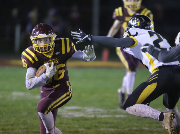 ROBERT  K. YOSAY | THE VINDICATOR..SR #26 Brennan Toy ducks away from Gmen #23 Jarrod Peters as he scampers for a first down..James A Garfield - G-Men  vs South Range Raiders at South Range Stadium..-30-