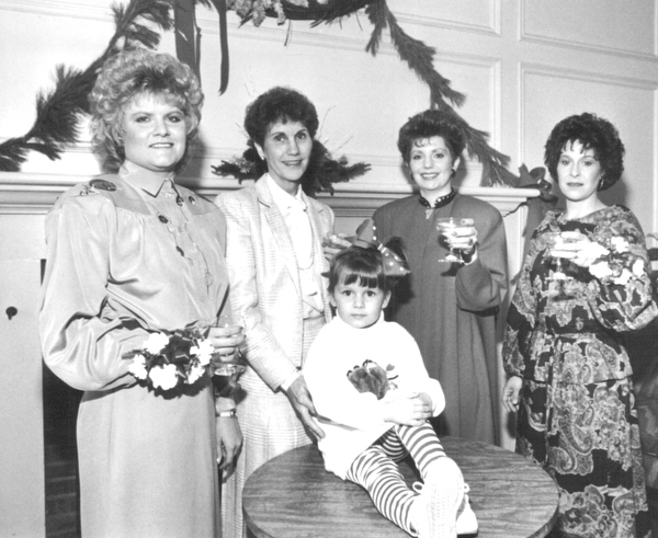 12041987 Warren Junior Women's League Champagne Luncheon Margo Hiller, a modelsitting on table, and from left, Valerie Burke, Barbara Anderson, Nancy Merio and susan Burkey.