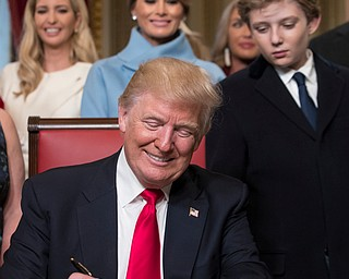President Donald Trump, joined by the Congressional leadership and his family, formally signs his cabinet nominations into law, Friday, Jan. 20, 2017, in the President's Room of the Senate on Capitol Hill in Washington Behind him are, from left, daughter Ivanka Trump, his wife Melania Trump, and his son Barron Trump. (AP Photo/J. Scott Applewhite, Pool)