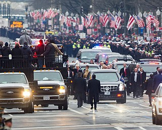 President Donald Trump and his wife Melania, center, walk during the Inaugural Parade on Pennsylvania Avenue, in Washington, Friday, Jan. 20, 2017. (AP Photo/Cliff Owen)