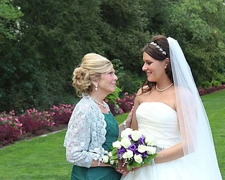 Mother of the bride Maribeth Bieber of North Lima and her daughter, Heather Scott of New Waterford, share a quiet moment at Heather's wedding.