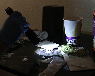 A police officer shines a flashlight onto a bag of Fentanyl found open on a bookshelf as Youngstown Police search a house on the 200 block of E Judson Ave, Thursday, June 1, 2017 in Youngstown. The bag was sampled and field tested on scene...(Nikos Frazier | The Vindicator)