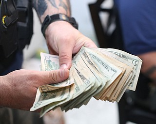 A police officer fans out a stack of money as it is counted and bagged as evidence as Youngstown Police search a house on the 200 block of E Judson Ave, Thursday, June 1, 2017 in Youngstown...(Nikos Frazier | The Vindicator)
