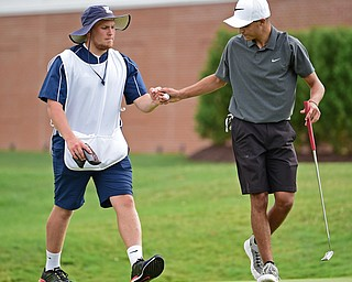 WARREN, OHIO - JULY 22, 2017: Jimmy Graham gets a fist bump from his caddie Ryan Lee after completing his round, Saturday afternoon at the Vindicator's Greatest Golfer of the Valley Jr. Championship at Avalon Lakes. DAVID DERMER | THE VINDICATOR