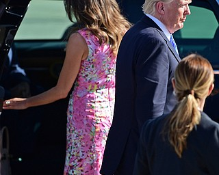 President Donald Trump walks while first lady Melania Trump enters a car at the Youngstown-Warren Regional Airport, Tuesday, Tuesday, July 25, 2017, in Vienna, Ohio. Trump will be speaking at a rally Tuesday at the Covelli Centre in Youngstown, Ohio. (David Dermer/The Vindicator via AP)