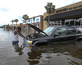 John Duke tries to figure out how to salvage his flooded vehicle in the wake Hurricane Irma, Monday, Sept. 11, 2017, in Jacksonville, Fla. (AP Photo/John Bazemore)