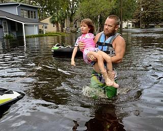 Tommy Nevitt carga a Miranda Abbott de seis años a través de una inundación provocada por el huracán Irma en la parte oeste de la ciudad de Jacksonville, Florida, el lunes 11 de septiembre de 2017. (Dede Smith/The Florida Times-Union vía AP)