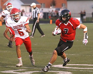 Canfield wide receiver Matt Zaremski(7) runs the ball in the first half as Struthers takes on Canfield, Friday, Sept. 22, 2017, at Canfield High School in Canfield. Struthers defensive back Adrian Brown(6) follows behind...(Nikos Frazier | The Vindicator)..