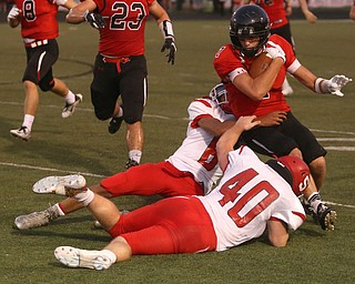 Canfield wide receiver Matt Zaremski(7) is taken down by Struthers defensive back Adrian Brown(6) and Struthers fullback Nate Richards(40) in the first half as Struthers takes on Canfield, Friday, Sept. 22, 2017, at Canfield High School in Canfield. ..(Nikos Frazier | The Vindicator)..