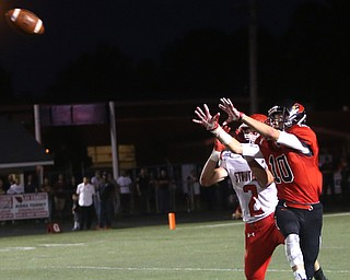 Canfield wide receiver Dean Cutrer(10) and Struthers defensive back Nick Adams(2) jump up for the pass intended for Cutrer in the first half as Struthers takes on Canfield, Friday, Sept. 22, 2017, at Canfield High School in Canfield. ..(Nikos Frazier | The Vindicator)..