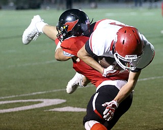 Struthers wide receiver Kevin Caldwell(89) is brought down by Canfield defensive back Paul French(27) in the first half as Struthers takes on Canfield, Friday, Sept. 22, 2017, at Canfield High School in Canfield. ..(Nikos Frazier | The Vindicator)..