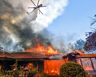 A helicopter dumps water on a home as firefighters battle a wildfire in Anaheim Hills in Anaheim, Calif., Monday, Oct. 9, 2017. Wildfires whipped by powerful winds swept through Northern California sending residents on a headlong flight to safety through smoke and flames as homes burned. (Jeff Gritchen/The Orange County Register via AP)