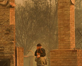 Darin Garcia looks at the remains of his home he's lived in for nearly 40 years as he embraces Ashley Alva, Monday Oct. 9, 2017 in the Coffey Park area of Santa Rosa, Calif. More than a dozen wildfires whipped by powerful winds been burning though California wine country. The flames have destroyed at least 1,500 homes and businesses and sent thousands of people fleeing. (Kent Porter/The Press Democrat via AP)