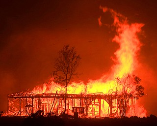 The Historic Round Barn burns, Monday Oct. 9, 2017, in Santa Rosa, Calif. More than a dozen wildfires whipped by powerful winds been burning though California wine country. The flames have destroyed at least 1,500 homes and businesses and sent thousands of people fleeing. (Kent Porter/The Press Democrat via AP)