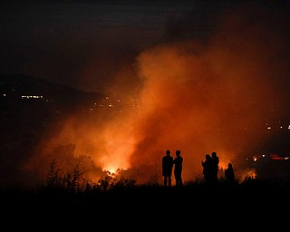 People watch as a wildfire burns along a hillside Monday, Oct. 9, 2017, in Orange, Calif. Authorities say at least half a dozen homes have burned in a fast-moving brush fire in Southern California. (AP Photo/Jae C. Hong)