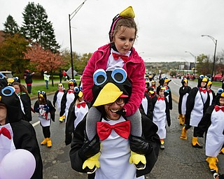 YOUNGSTOWN, OHIO - OCTOBER 28, 2017: Paisley McKee of Cortland rides on the shoulder of David Kovacs from Cortland while they are both dressed as penguins while marching on Fifth Avenue during the YSU homecoming parade, Saturday afternoon. DAVID DERMER | THE VINDICATOR