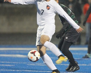 WILLIAM D LEWIS  | THE VINDICATOR..Howlands #7 Steven Glisic moves the ball away from Aurora #41  Rees Jones during first half action Division II regional semifinal boys soccer Howland vw Aurora at Ravenna Stadium..-30-