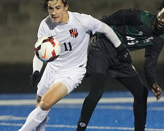 WILLIAM D LEWIS  | THE VINDICATOR..Howlands #11 Jonah Wiseman chases after the ball as  Aurora #49  Alex Bibza  looks on..Division II regional semifinal boys soccer Howland vw Aurora at Ravenna Stadium..-30-