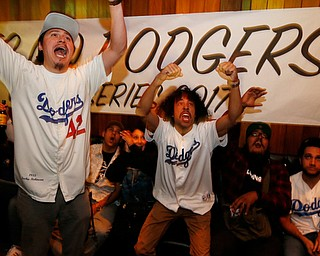 Los Angeles Dodgers fans Mescal Miranda, left, and Max Perez react as they watch the fifth inning of Game 7 of baseball's World Series between the Houston Astros and the Dodgers at The Short Stop bar in Echo Park neighborhood of Los Angeles, Wednesday, Nov. 1, 2017. (AP Photo/Damian Dovarganes)