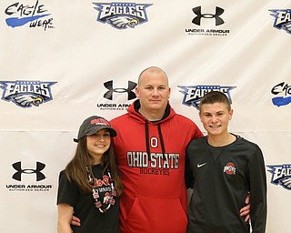 Claire Gagliardi(left) poses for photos with her father, Tony(center), and brother, Anthony, Wednesday, Nov. 8, 2017, in the Hubbard High School Gymnasium in Hubbard. Gagliardi plans on attending Ohio State University to play gymnastics...(Nikos Frazier | The Vindicator)