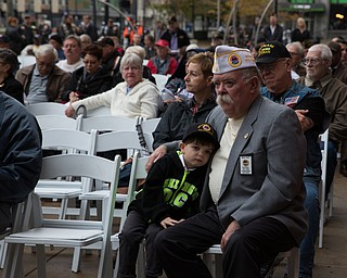 Rebecca Devereaux | The Vindicator ..Four-year-old Corey Riley of Pittsburgh leans on his grandfather Rege Riley, American Veterans First Vice Commander of Pittsburgh, during the annual Laying of the Roses Ceremony in Downtown Youngstown on Sunday.