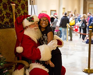 Shayna Stewart, 10 of Austintown takes a photo with Santa at the Butler Institute of American Art Family Day on Sunday at the musuem in Youngstown.