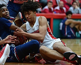 YOUNGSTOWN, OHIO - NOVEMBER 29, 2017: Youngstown State's Michael Akuchie attempts to rip the ball away from Robert Morris's Dachon Burke during the first half of their game Wednesday night at Beeghley Center. Robert Morris won 81-74. DAVID DERMER | THE VINDICATOR