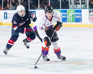 Scott R. Galvin | The Vindicator.Youngstown Phantoms right wing Chase Gresock (19) skates the puck to the goal past USA NTDP's Case McCarthy during the second period at the Covelli Centre on Friday night.