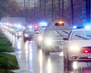 William D. Lewis The Vindicator Police escort/motorcade escorting body of slain Girard PD office Justin Leo makes its way up Churchill Rd. in girard Monday afternoon. The body was being transported to Blackstoine Funeral home after an autopsy in Cuyahoga county.