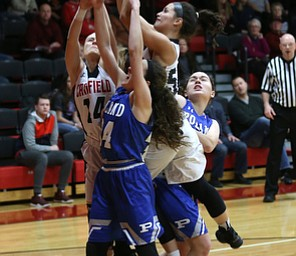 Canfield guard Serena Sammarone (54) gets the rebound  from Canfield guard Emerson Fletcher (14) Poland guard Kat Partika (22) and Poland guard Gabby Romano (34) in the first quarter of an AAC high school basketball game, Friday, Dec. 23, 2017, in Canfield. Canfield won 45-34...(Nikos Frazier | The Vindicator)