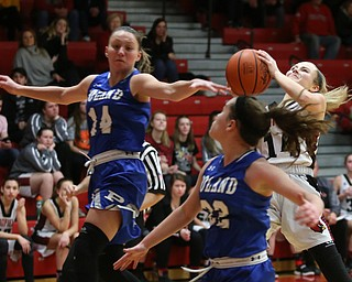 Canfield guard Emerson Fletcher (14) goes up for a layup as Poland forward Kailyn Brown (14) and Poland guard Kat Partika (22) fly past her in the third quarter of an AAC high school basketball game, Friday, Dec. 23, 2017, in Canfield. Canfield won 45-34...(Nikos Frazier | The Vindicator)