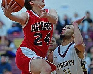LIBERTY, OHIO - DECEMBER 27, 2017: Mathews Zak Arnio goes to the basket against Liberty's Kevin Code during the first half of their game on Wednesday night at Liberty High School. DAVID DERMER | THE VINDICATOR