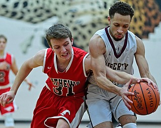 LIBERTY, OHIO - DECEMBER 27, 2017: Liberty's Kevin Code controls the ball while Mathews Zach Rhodanz attempts to knock it out of his control during the second half of their game on Wednesday night at Liberty High School. DAVID DERMER | THE VINDICATOR