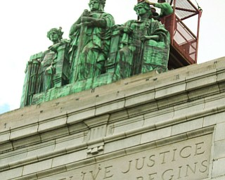 ROBERT K. YOSAY  | THE VINDICATOR..the newly-restored copper statues were returned to its roof of the courthouse..The statues, removed in October 2010, have been returned to their perch above the courthouse's main entrance where they had sat since 1909...The three hollow statues, which were restored by an Oberlin firm, are named ÒJustice,Ó on the left, ÒStrength and AuthorityÓ in the center; and ÒLawÓ on the right.