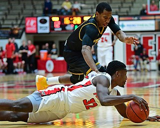 YOUNGSTOWN, OHIO - JANUARY 4, 2017: Youngstown State's Garrett Covington falls to the floor to grab the ball away from Milwaukee's Jeremiah Bell during the first half of their game, Thursday night at Beeghly Center. DAVID DERMER | THE VINDICATOR