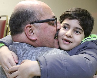 William D. Lewis the Vindicator  Al Adi kisses Heider Haddad, 7, during a vicotry party at The Arab American Community Center 1-6-18. Adi won a stay of Deportation Heider is a son of Fawsi and Karma Haddad of Liberty who are friends of Adi.