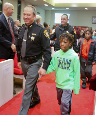 William D. Lewis the Vindicator Trumbull County Sheriff Paul Monroe wals shand in hand with Devin Sanders, 7, during a MLK Celebration Service at Second Baptist Church in Warren 1-14-18. A number of area officers attending the service and were escorted by local children.