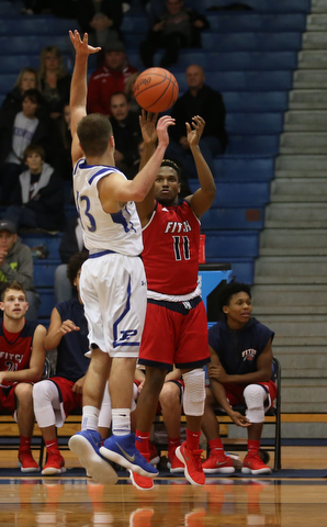 Austintown Fitch guard Emaniel Dawkins (11) goes up for three as Poland guard Bradon Barringer (13) attempts to block his shot in the third quarter of an AAC high school basketball game, Tuesday, Jan. 16, 2018, in Poland. Poland won 70-56...(Nikos Frazier | The Vindicator)