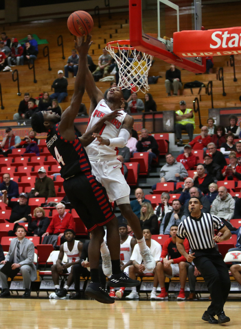 Youngstown State guard Braun Hartfield (1) goes up for a layup against UIC guard Tarkus Ferguson (4) in the first half of a NCAA college basketball game, Thursday, Jan. 18, 2018, in Youngstown. UIC won 92-78...(Nikos Frazier | The Vindicator)