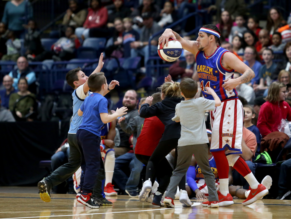 Globetrotter the shot keeps the ball away from a group of kids, Jan. 24, 2018, at the Covelli Centre in Youngstown...(Nikos Frazier | The Vindicator)