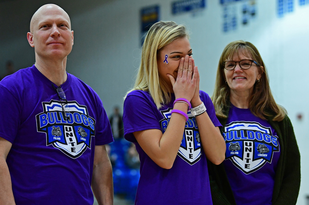 POLAND, OHIO - JANUARY 26, 2018: Lakeview student Alexis Rygalski reacts after hearing the total of the money raised for her treatment while standing not he court with her parents Hope and Mike Rygalski during the second half between Lakeview and Poland on Friday night at Poland High School. DAVID DERMER | THE VINDICATOR