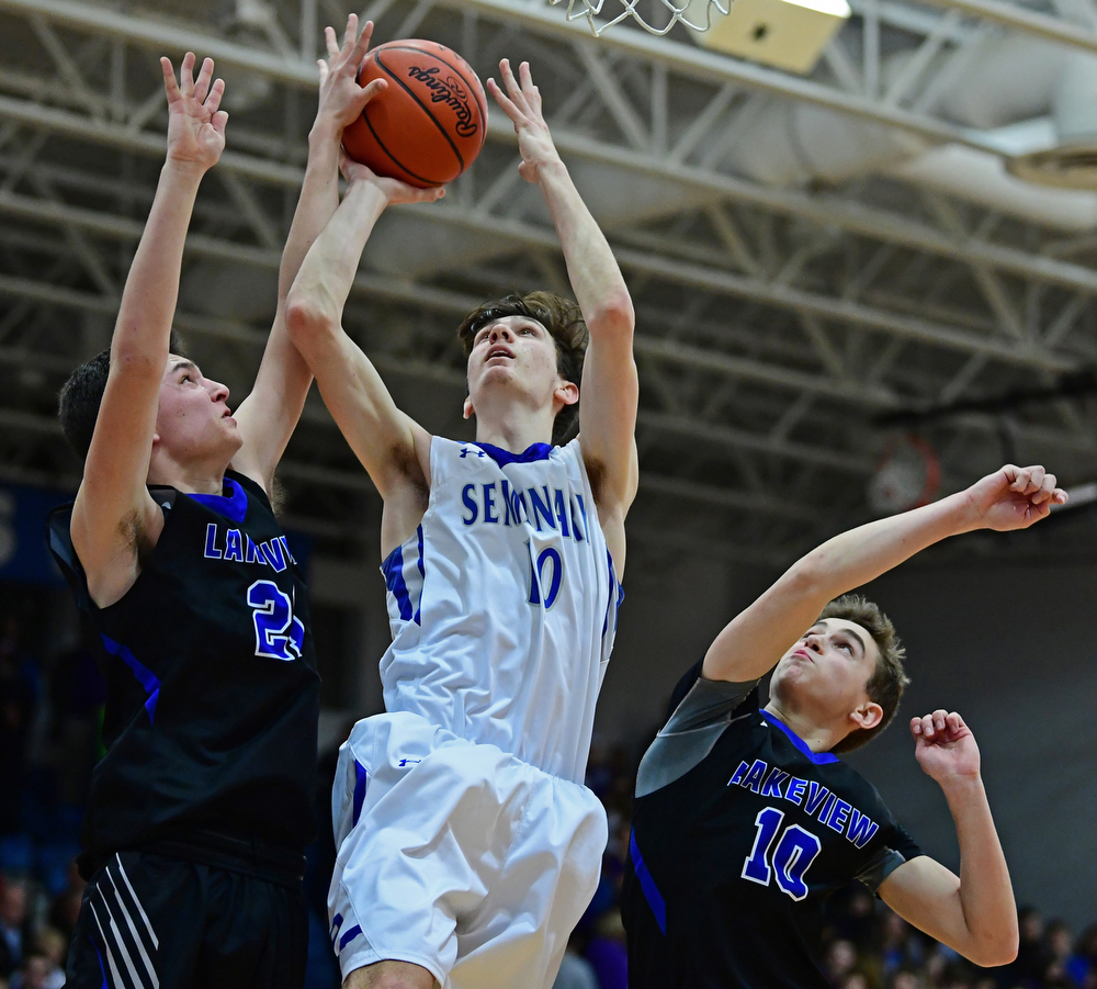 POLAND, OHIO - JANUARY 26, 2018: Poland's Daniel Kramer, center, goes to the basket against Lakeview's Jeff Remmick and AJ McClellan, right, during the second half of their game on Friday night at Poland High School. DAVID DERMER | THE VINDICATOR