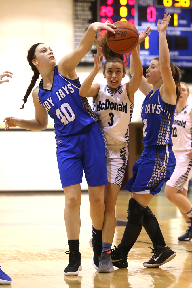 McDonald's Olivia Perry (3) is stripped of the ball by Jackson-Milton forward Abigail Spalding (40) and Jackson-Milton guard Julia Bogden (2) in the first half of an Mahoning Valley Athletic Conference high school basketball game, Monday, Jan. 29, 2018, in McDonald. McDonald won 37-34...(Nikos Frazier | The Vindicator)