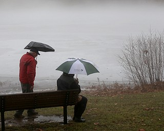 Bob and Judith Stanger of Boardman sit on a bench at Glacier Lake looking at the fog layer created by warm rain interacting with the ice layer on the surface of the lake, Thursday, Jan. 11, 2018, in Mill Creek Park. ..(Nikos Frazier | The Vindicator)