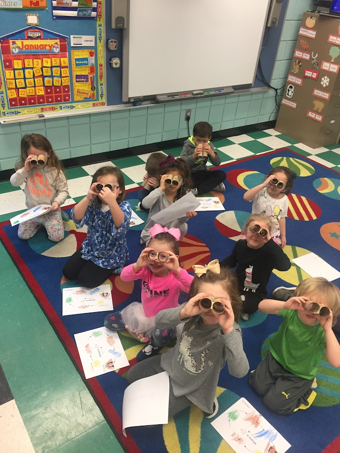 "Above, students of Barbara Conti, a Preschool Enrichment class teacher at Ursuline Preschool and Kindergarten, are studying bears and their habitats. The students made maps and ""binoculars"" to help them search for the cave and bears."