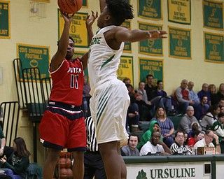 Austintown Fitch guard Emaniel Dawkins (11) goes up for three as Ursuline guard Cameron Lawrence (4) attempts to block his shot in the first quarter of an OHSAA high school basketball game, Tuesday, Feb. 13, 2018, in Youngstown. Ursuline won 63-58...(Nikos Frazier | The Vindicator)