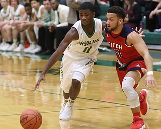 Ursuline guard Nicolas Venzeio (11) drives past Austintown Fitch forward Randy Smith (0) in the second quarter of an OHSAA high school basketball game, Tuesday, Feb. 13, 2018, in Youngstown. Ursuline won 63-58...(Nikos Frazier | The Vindicator)