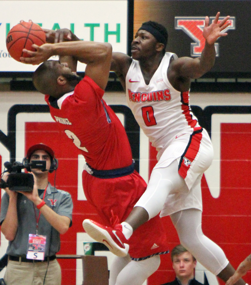 William D. Lewis The Vindicator  YSU'sTyree Robinson(0) fouls Detroit's Roschon Prince(2) during 2-16-18 action at YSU.