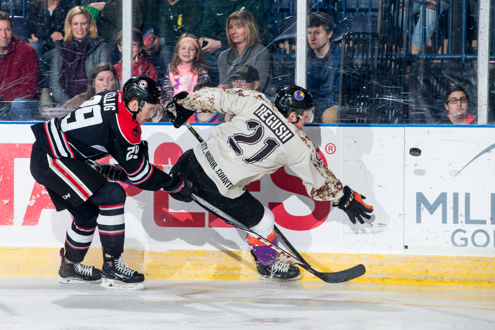 Scott R. Galvin | The Vindicator.Youngstown Phantoms center Mike Regush (21) gets checked into the board by Waterloo Black Hawks defenseman Hunter Lellig (29) during the first period at the Covelli Centre on Saturday, February 17, 2018.